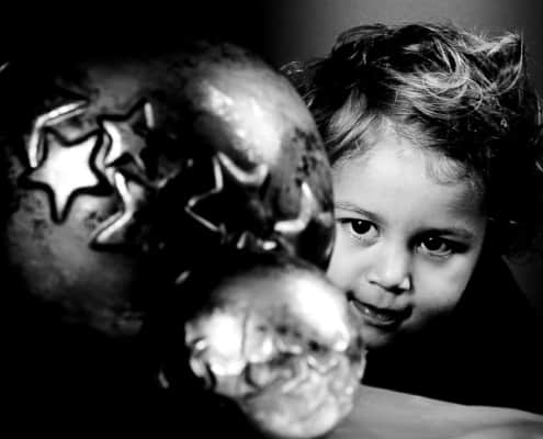 Ein Kind betrachtet fasziniert zwei Weihnachtskugeln